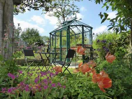 Aluminium greenhouse and patio set in garden